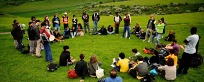 A group of people in a circle hold a group discussion outside